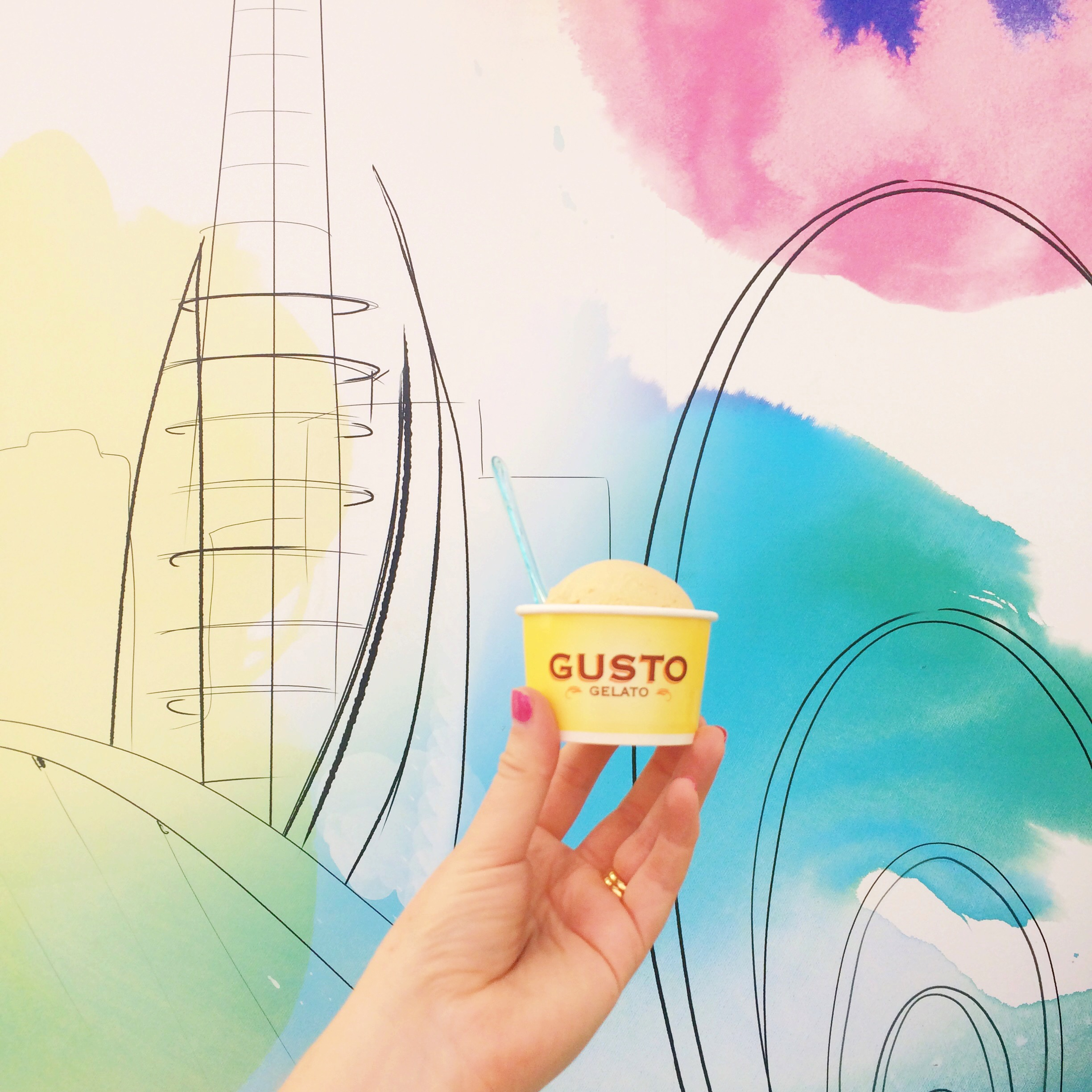 Gusto gelato ice cream held up in front of colourful store artwork