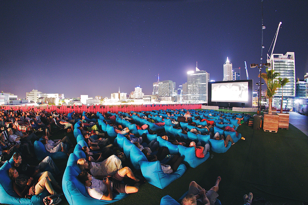 View of audience watching movie on rooftop with City in background