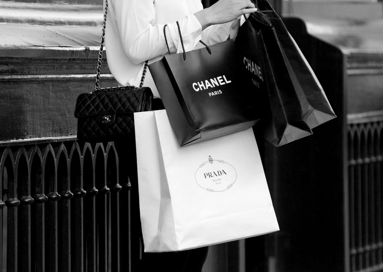 Person holding Chanel and Prada shopping bags